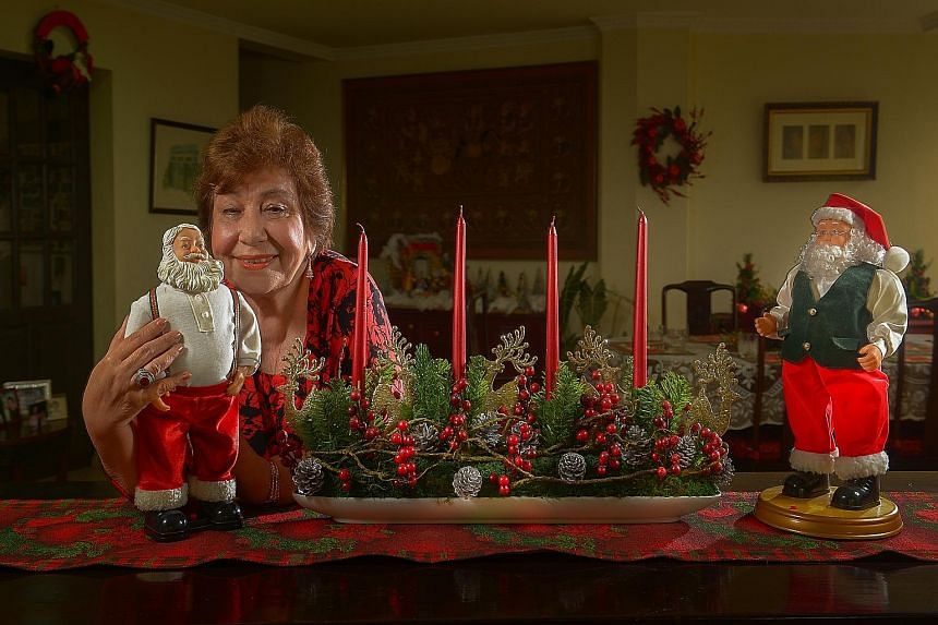 Retiree Dorothy Tessensohn at her Jervois Road apartment with her battery- powered dancing and chuckling Santa Claus figurines.