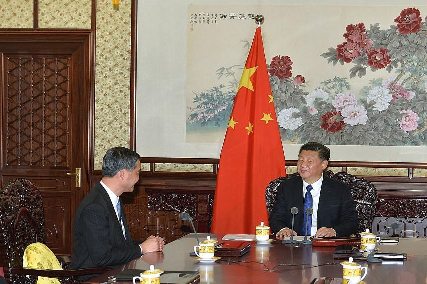 Hong Kong Chief Executive Leung Chun Ying (left), seated at one side of a conference table, during a meeting with Chinese President Xi Jinping in Beijing on Wednesday.