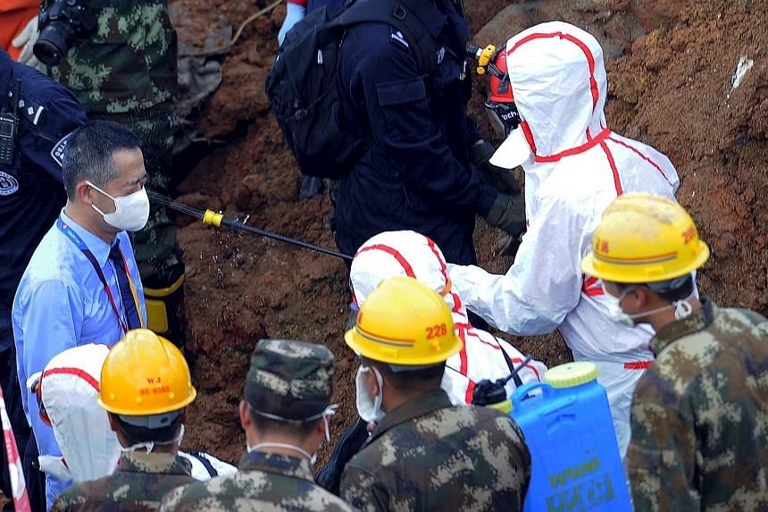 A medical personnel spraying disinfectant over a rescuer at an industrial park in Shenzhen that was hit by the landslide on Sunday. Only one man was rescued on Wednesday, and hopes of finding more survivors are growing dim.