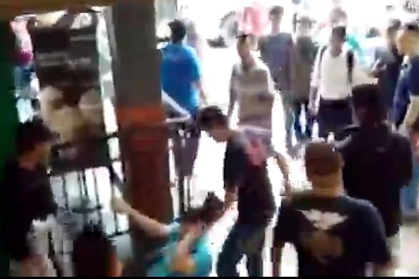 A phone seller (in light blue top, on the ground) being beaten up at Kota Raya mall on Sunday. Some 20 Malay men attacked cellphone sellers in the mall after allegations that a store had cheated a Malay customer.