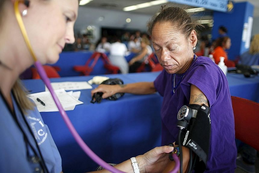 Ms Valerie Caesar, 46, having her blood pressure taken in October at the Care Harbor four-day free clinic, which offers free medical, dental and vision care to around 4,000 uninsured people in Los Angeles, California.