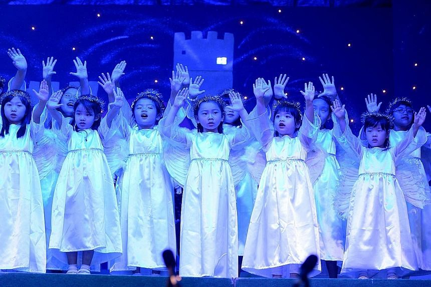 Sunbeams Children's Choir at Wesley Methodist Church on Wednesday. Many people were out shopping before Christmas, taking in decorations like the fairy tale-themed tree at Raffles City mall (below). Lemurs hunting for food in a Christmas tree-shaped