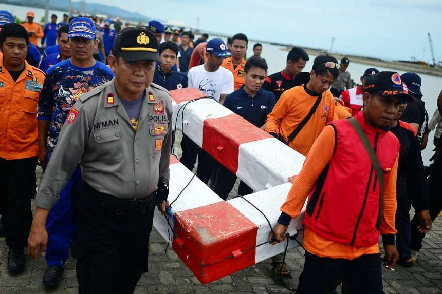 Indonesian rescue workers carry a floatation device believed to belong to the capsized ferry at a sea port in Siwa, South Sulawesi, Indonesia, Dec 21, 2015.