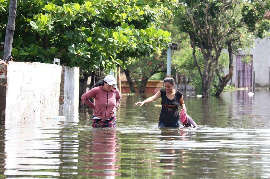 Women walk in a flooded street in Asuncion.