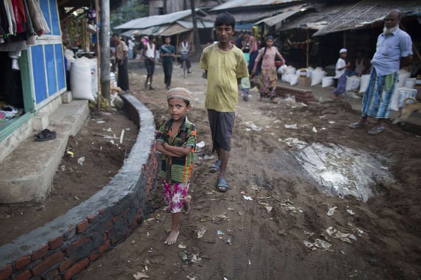 A Rohingya boy and elders walk at a market near Thel-Chaung displacement camp in Sittwe located in Rakhine State on Nov 8, 2015.