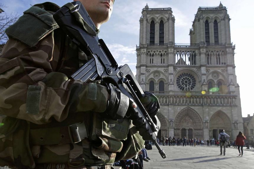 An armed French soldier patrols in front of Notre Dame Cathedral in Paris on Dec 24, 2015.
