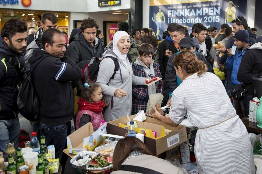 Volunteers distribute food and drink to migrants arriving at Malmo train station in Sweden in September 2015.