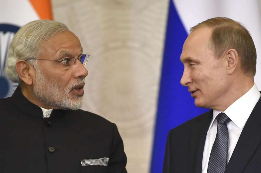 Putin (right) listens to Modi during a signing ceremony following their meeting.