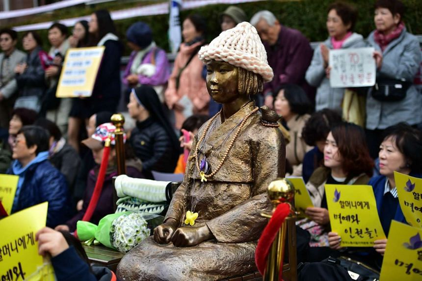 Protestors sit next to a statue  called the Peace Monument for former comfort women.