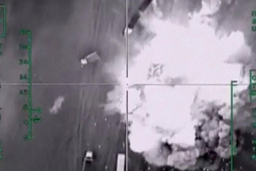 A frame grab taken from footage released by Russia's Defence Ministry on Dec 4, 2015, shows air strikes carried out by Russia's air force hitting trucks carrying oil, which, according to the ministry, are controlled by the Islamic State militants, in