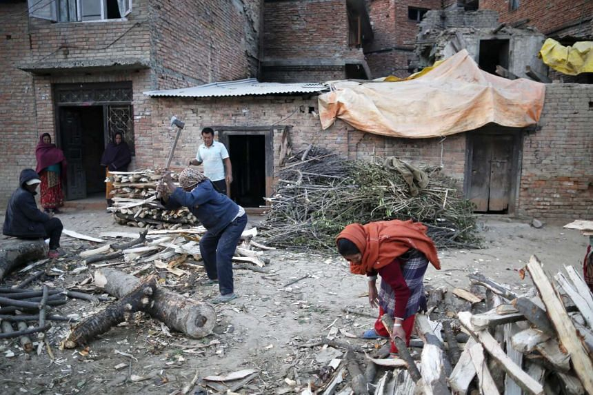 Nepalese who lost their home in the April 25 earthquake chop firewood in Lalitpur, Nepal.