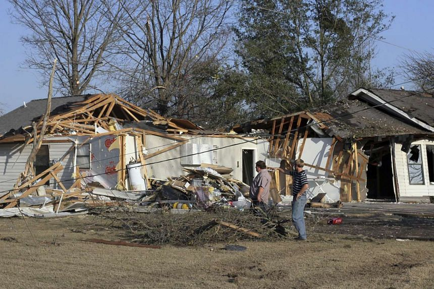 People assess the damage to a house after a powerful tornado struck Clarksdale, Mississippi.