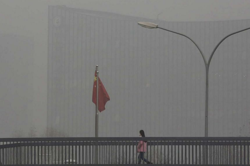 A woman wearing a protective mask walks past a Chinese national flag on a pedestrian overpass on a heavily polluted day in Beijing on Dec 25, 2015.
