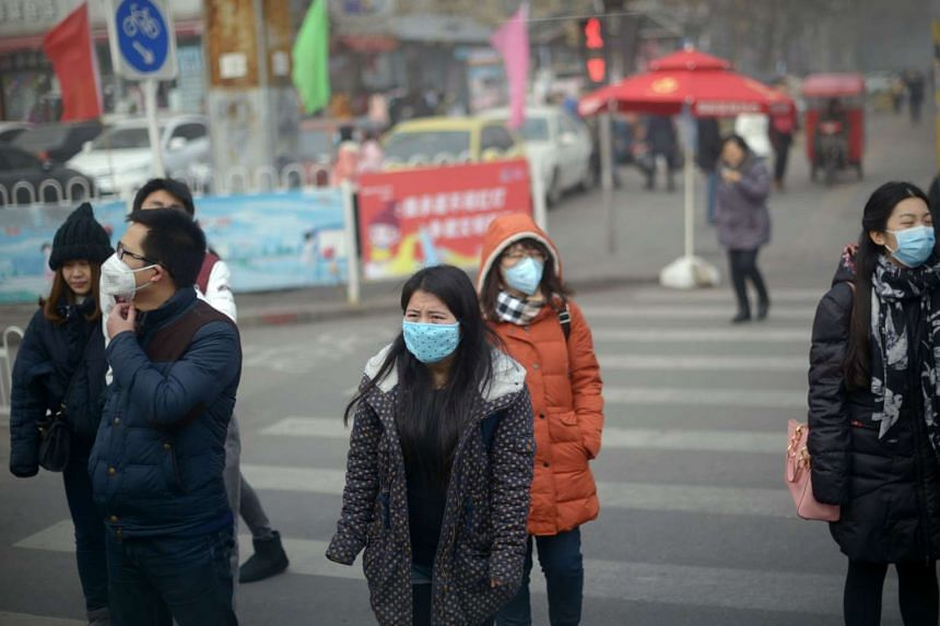 People crossing a street during heavy pollution in Beijing on Dec 25, 2015.