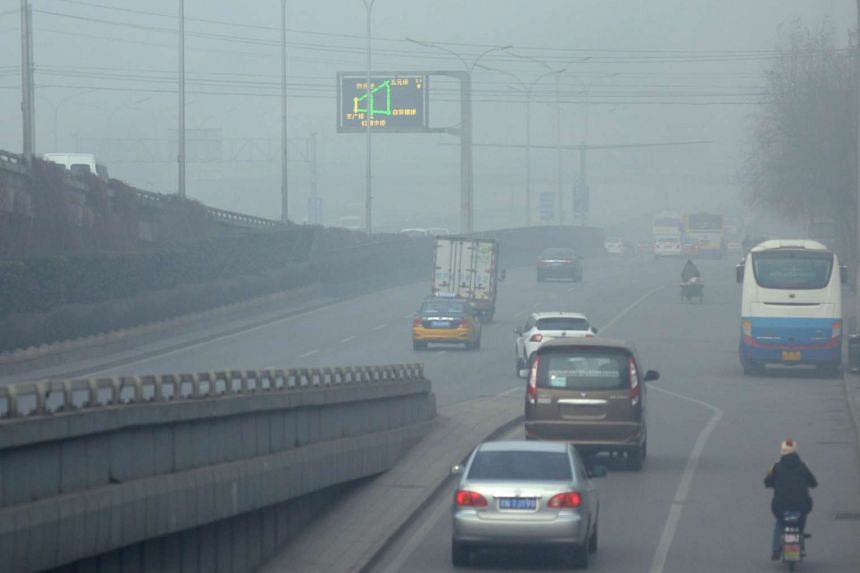 Cars driving along a road on a polluted day in Beijing on Dec 25, 2015.