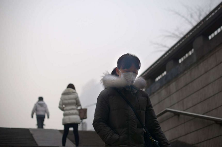 A woman wearing a mask prepares to walk through an underpass on a polluted day in Beijing on Dec 25, 2015.