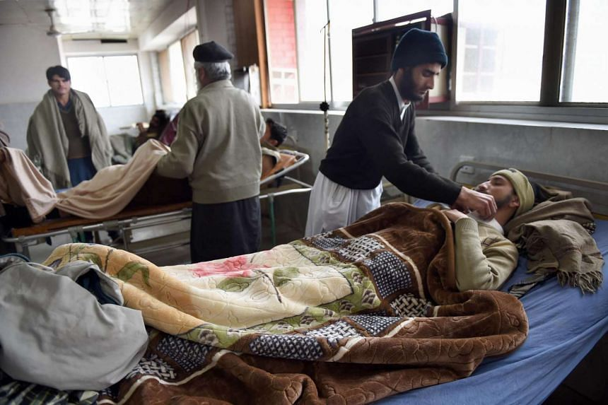 Pakistani relatives tend to an earthquake survivor as he is treated at a hospital in Peshawar on December 26, 2015.
