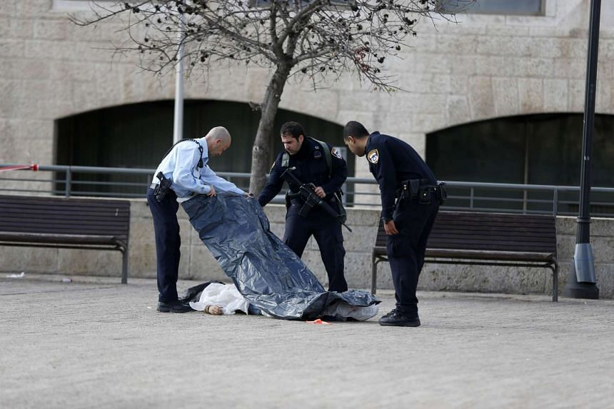 Israeli policemen cover the body of the Palestinian assailant who was shot dead following the reported attack.