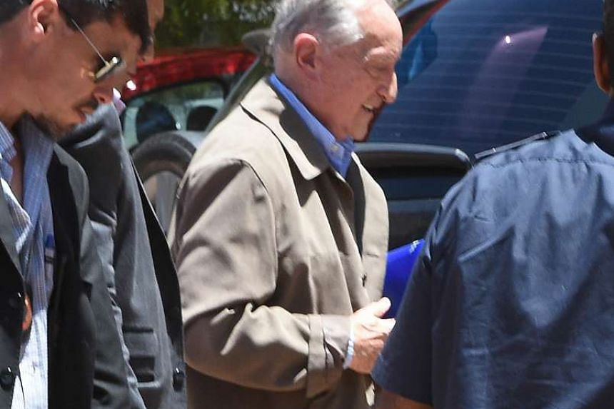 Figueredo (centre) is escorted as he arrives at court in Montevideo on Dec 24, 2015.