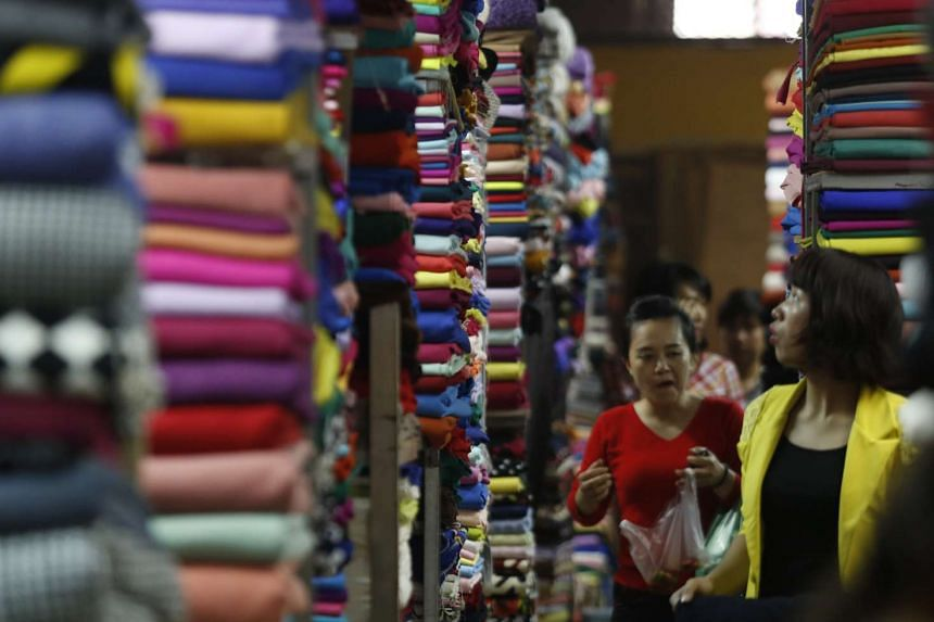 Customers walking along fabric rolls which are displayed for sale at a market in Hanoi, Vietnam on Dec 24, 2015. PHOTO: REUTERS