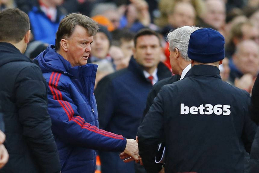 Manchester United manager Louis van Gaal (left) shakes hands with Stoke manager Mark Hughes (partially hidden) after his team lost 0-2 on Dec 26, 2015.