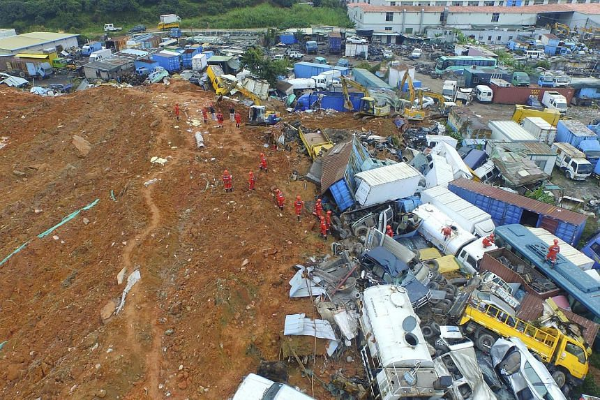 An aerial view shows rescuers walking among damaged vehicles to search for survivors at the site of a landslide which hit an industrial park in Shenzhen.