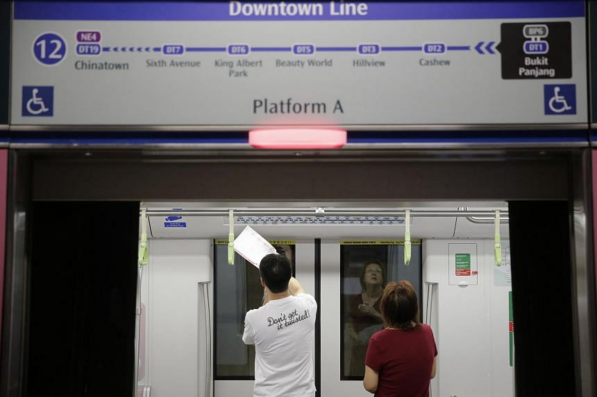 Commuters studying the route map in the train car at Bukit Panjang station of Downtown Line 2 on Dec 27, 2015.