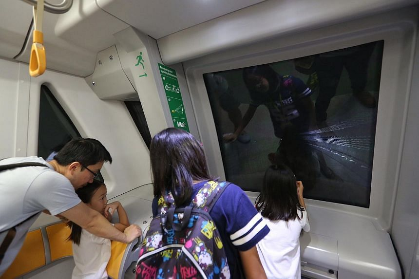 Commuters look at the train tracks along the tunnel as they travel along the Downtown Line 2 for the first time.