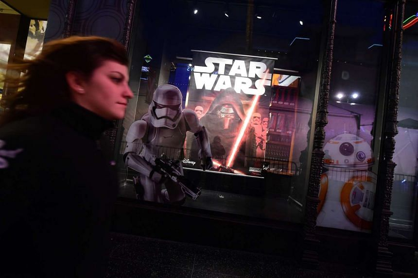 A woman rushes past a store selling Star Wars merchandise along Hollywood Boulevard for the premiere of the latest Star Wars film.