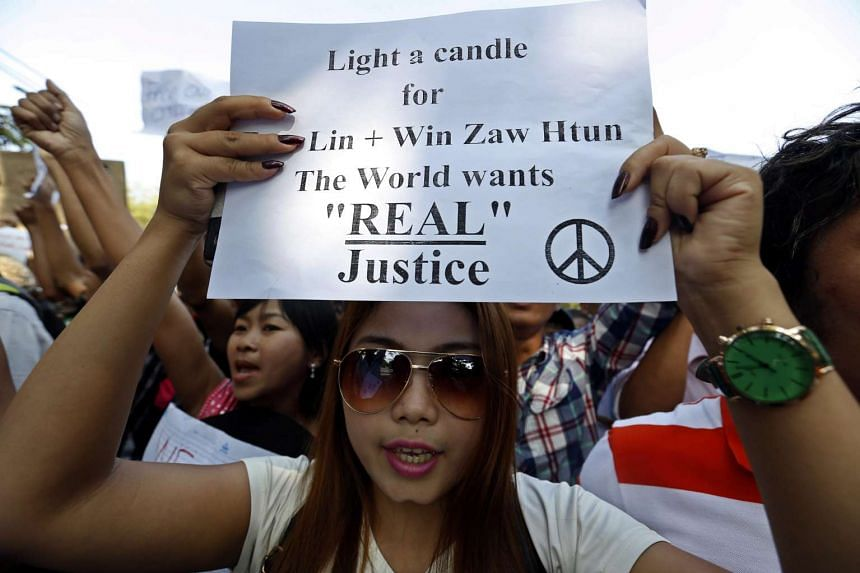 A protester holding a placard during a demonstration against a Thai court's death sentence for two Myanmar migrant workers, in front of Thailand's Embassy in Yangon, Myanmar, on Dec 26, 2015. Hundreds of protesters gathered in Yangon to express their