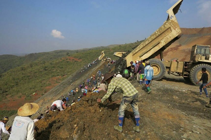 Workers are seen near the site of the landslide at a jade mine in Hpakant, Kachin State on Dec 27, 2015.