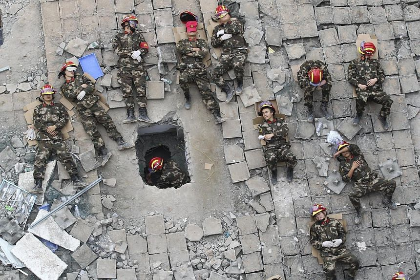 Rescuers resting among the debris of collapsed industrial buildings during a break in rescue operations in Shenzhen last Wednesday. There is some risk of more landslides at three separate places and professionals are dealing with the issue.