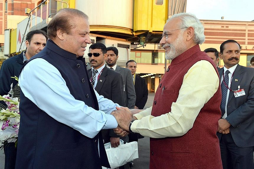 Indian Prime Minister Narendra Modi (above, right) is welcomed by the Prime Minister of Pakistan, Mr Nawaz Sharif, at the airport in Lahore, Pakistan, on Friday. The visit was initiated over a phone call Mr Modi made to greet Mr Sharif on his 66th bi