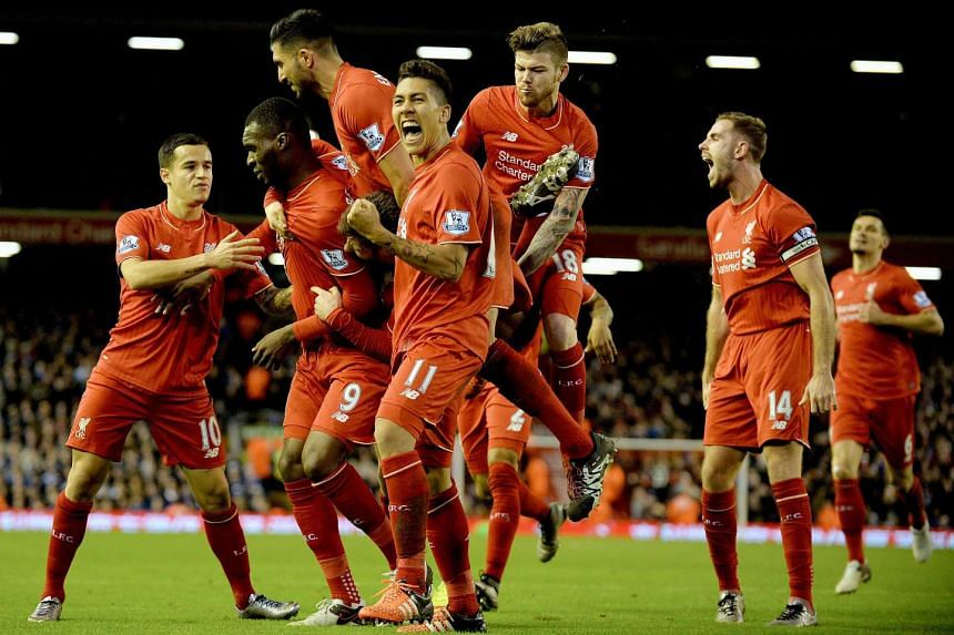 Liverpool players celebrate with Christian Benteke after he scores.