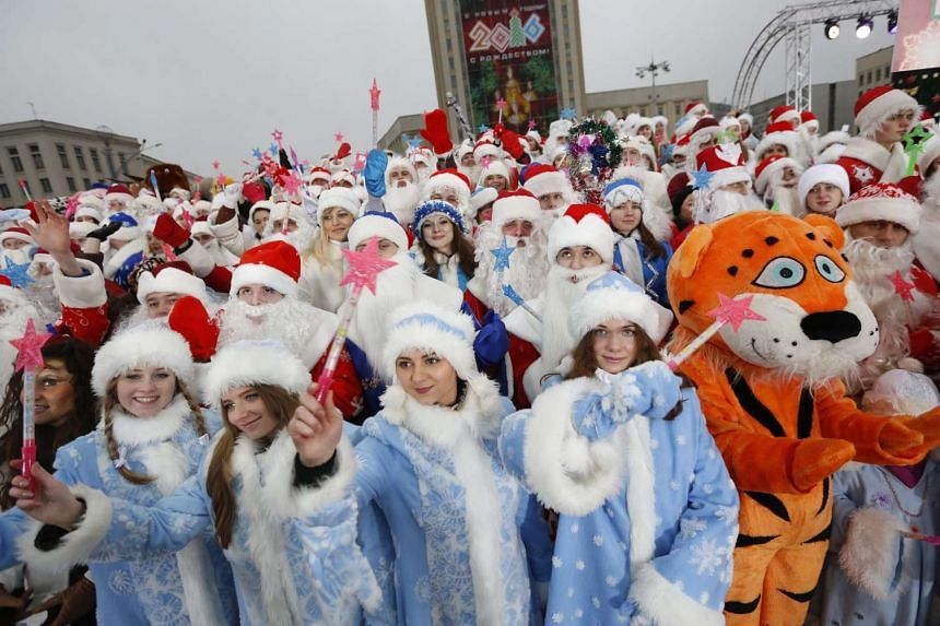 People taking part in a Christmas parade in the centre of Minsk, Belarus, on Christmas Day. In this winter tradition, the men put on Ded Moroz (Grandfather Frost) costumes while the women don Snegurochka (Snow Maiden) costumes.
