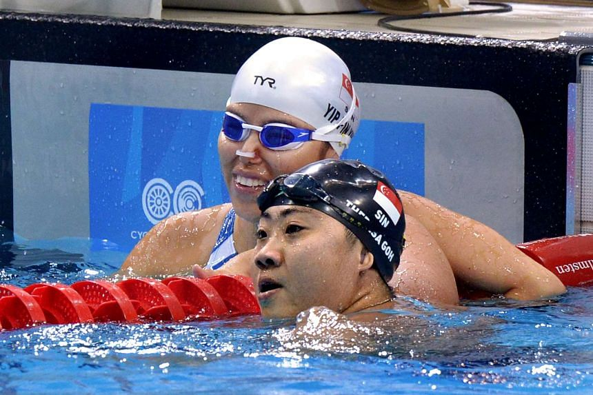 Yip Pin Xiu (left), with five-gold buddy Theresa Goh, took on rivals three classes higher and won, in a world-record breaking swim.