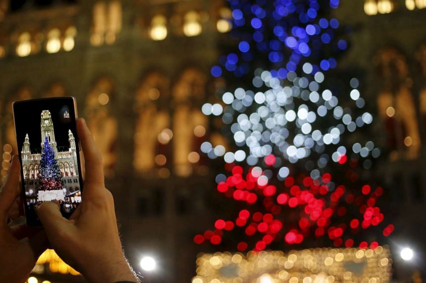 A Vienna tourist takes a picture of a Christmas tree lit in the colours of France's national flag to mark the Paris attacks.