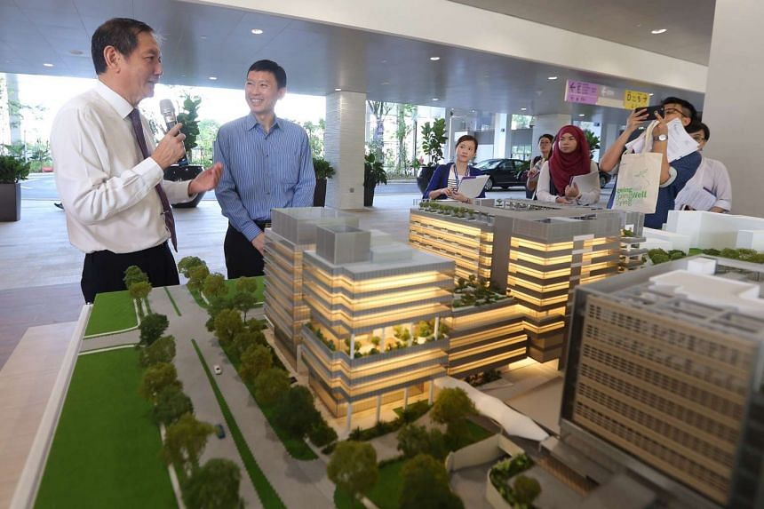 Group CEO of Alexandra Health System Mr Liak Teng Lit (extreme left) shows Minister of State for Health Mr Chee Hong Tat (second from left) a model for the completed Yishun Community Hospital.