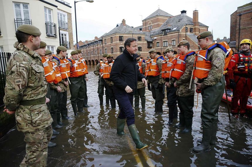British Prime Minister David Cameron (centre) greeting British soldiers doing flood relief work after the river Ouse burst its banks, in York, on Dec 28, 2015.