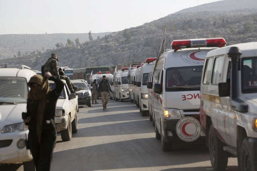 Fighters from a coalition of rebel groups escorting Syrian Arab Red Crescent ambulances evacuating fighters and civilians from al-Foua and Kefraya in Syria to Turkey, on Dec 28, 2015.