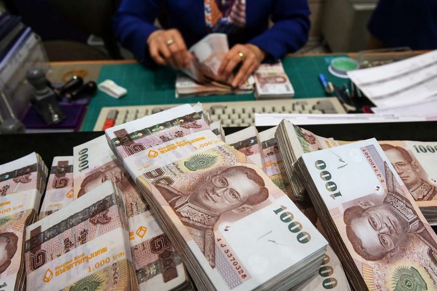 Bundles of one-thousand baht banknotes are arranged for a photograph inside a Bangkok Bank branch at the company's headquarters in Bangkok on Dec 12, 2013.