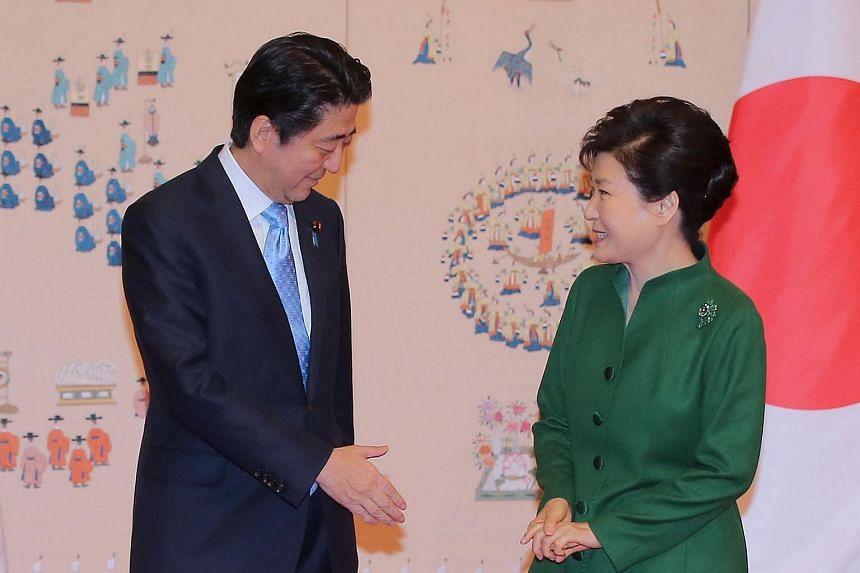 Japanese PM Shinzo Abe reaching to shake hands with South Korean President Park Geun Hye before a bilateral summit at the Presidential Blue House in Seoul on Nov 2, 2015.