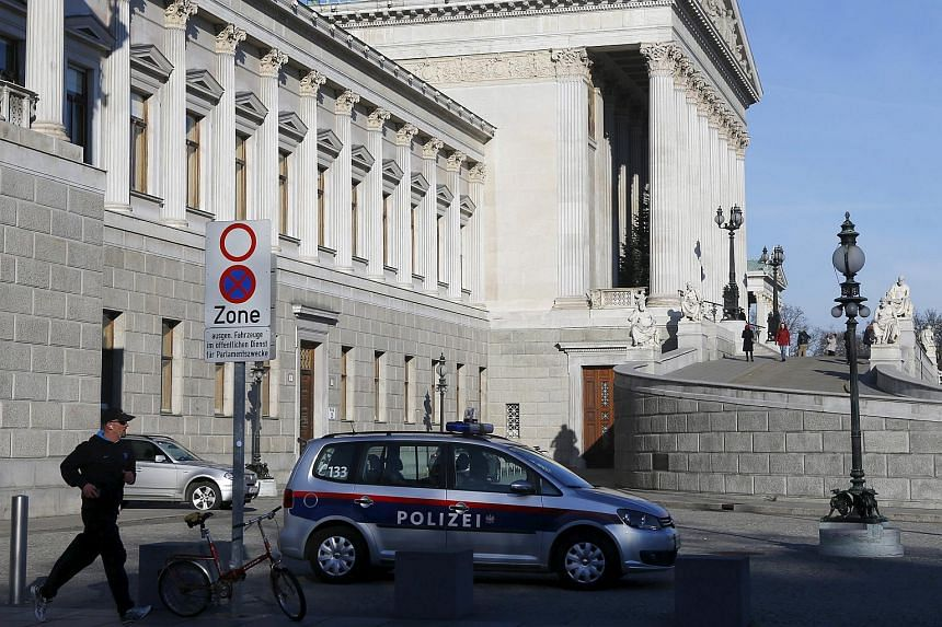 A man jogging past a police car parked in front of the parliament building in Vienna, Austria, on Dec 27, 2015.