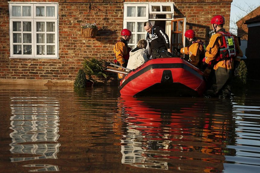 Members of the emergency services rescuing people from a flooded street in Naburn, northern England, on Dec 27, 2015.