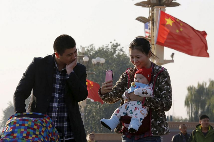 A couple taking a picture with their baby on the Tiananmen Gate in Beijing on Nov 2, 2015.