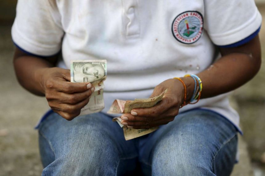 A Colombian Nukak Maku Indian woman counts money at a park in San Jose del Guaviare of Guaviare province on Sept 4, 2015.