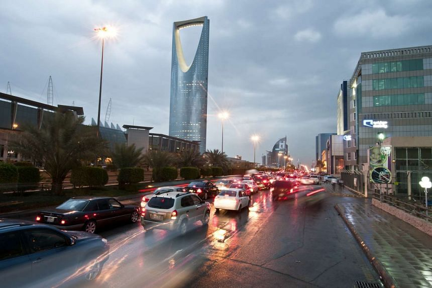 Traffic passes the Kingdom Tower, on King Fahad Road in Riyadh, Saudi Arabia.