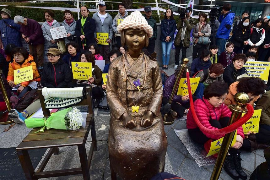 "Protestors sit next to the ""peace monument"" for former ""comfort women"" in Seoul on Nov 11, 2015."