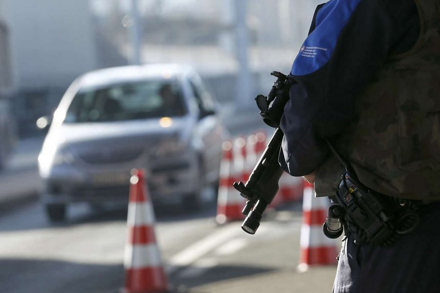 A heavily armed Swiss customs officer stands guard at the Swiss-French customs post of Bardonnex near Geneva.