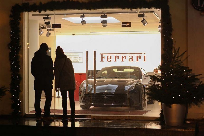 Pedestrians pause to look at a luxury sportscar on display at the Ferrari SpA showroom on Tretyakov Drive in Moscow, Russia on Dec 20.